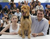 "Director Kornel Mundruczo (R) and cast member Zsofia Psotta (C) pose with a dog sitting on the desk during a photocall for the film ""Feher isten"" (White God) in competition for the category ""Un Certain Regard"" at the 67th Cannes Film Festival in Cannes May 17, 2014.                 REUTERS/Regis Duvignau"