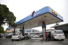 Un trabajador en una gasolinera de PDVSA en Caracas, dic 16 2013. La estatal Petróleos de Venezuela (PDVSA) firmó el miércoles una línea de crédito de más de 2.000 millones de dólares de tres grandes empresas de servicios petroleros, dijo el ministro de Petróleo y Minería del país sudamericano, Rafael Ramírez. REUTERS/Carlos Garcia Rawlins
