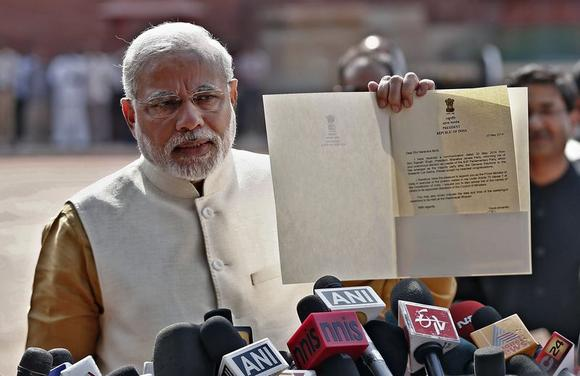 Narendra Modi shows to the media a letter which he received from President Pranab Mukherjee after meeting him at the Presidential Palace in New Delhi May 20, 2014. REUTERS/Adnan Abidi