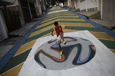 "Gabriel, 14, plays soccer on graffiti painted with the official match ball for the 2014 World Cup named ""Brazuca"" on a street in Sao Paulo May 14, 2014. REUTERS/Nacho Doce"