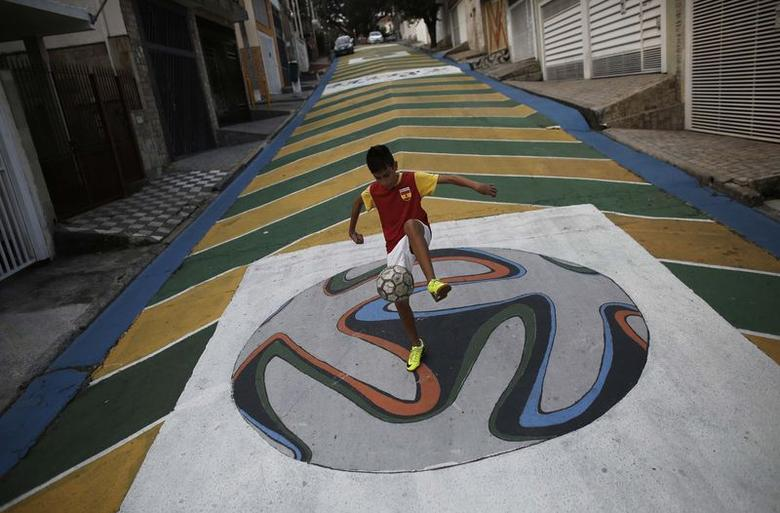 Gabriel, 14, plays soccer on graffiti painted with the official match ball for the 2014 World Cup named ''Brazuca'' on a street in Sao Paulo May 14, 2014. REUTERS/Nacho Doce