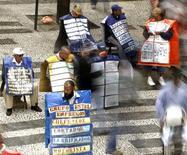 Personas con anuncios de empleos en una calle del centro de Sao Paulo, mayo 24 2005. La tasa de desempleo de Brasil bajó inesperadamente en abril a pesar de la debilidad del crecimiento del empleo ya que se redujo la cantidad de personas buscando trabajo, mostraron el jueves los datos del gobierno.   REUTERS/Paulo Whitaker