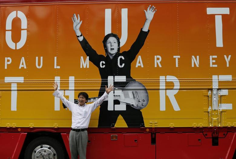 A man poses for a photo in front of a truck with an advertisement for singer Paul McCartney's ''Out There'' tour, after the cancellation of McCartney's concert at the Nippon Budokan in Tokyo May 20, 2014.   REUTERS/Issei Kato