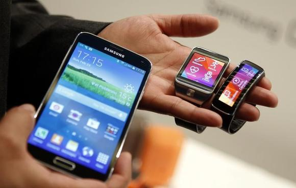 The new Samsung Galaxy S5 smartphone (L), Gear 2 smartwatch (C) and Gear Fit fitness band are displayed at the Mobile World Congress in Barcelona February 23, 2014. REUTERS/Albert Gea/Files