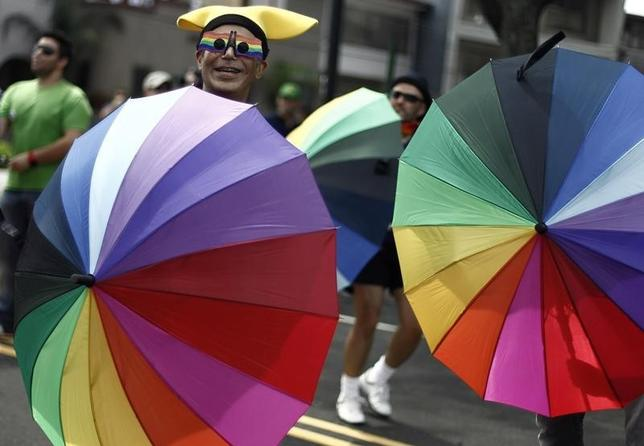 Revellers with rainbow-coloured umbrellas take part in an annual gay pride parade in San Jose July 1, 2012.  REUTERS/Juan Carlos Ulate