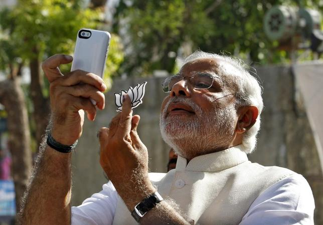 Narendra Modi takes a ''selfie'' with a mobile phone after casting his vote at a polling station during the seventh phase of India's general election in Ahmedabad April 30, 2014. REUTERS/Amit Dave