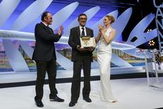 "Director Nuri Bilge Ceylan (C), Palme d'Or award winner for his film ""Winter Sleep"", poses on stage surrounded by director Quentin Tarantino (L) and actress Uma Thurman (R) during the closing ceremony of the 67th Cannes Film Festival in Cannes May 24, 2014.  REUTERS/Yves Herman"
