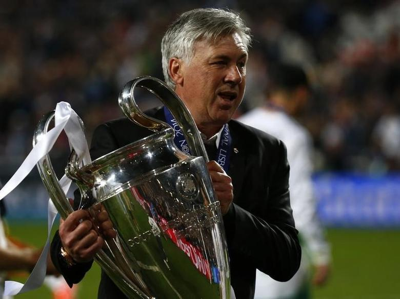 Real Madrid's coach Carlo Ancelotti holds the trophy after defeating Atletico Madrid in their Champions League final soccer match at the Luz Stadium in Lisbon, May 24, 2014.       REUTERS/Michael Dalder