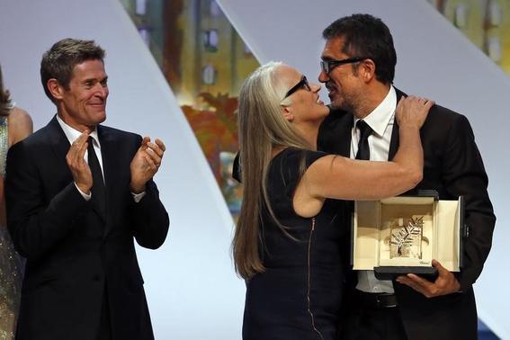 Jury President Jane Campion (C) kisses director Nuri Bilge Ceylan (R), Palme d'Or award winner for his film 'Winter Sleep', as jury member actor Willem Dafoe applauds during the closing ceremony of the 67th Cannes Film Festival in Cannes May 24, 2014. REUTERS/Eric Gaillard