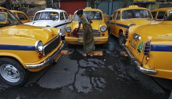 Sumitra Sarkar, 35, cleans a yellow ambassador taxi at a parking area along a roadside in Kolkata March 8, 2014. REUTERS/Rupak De Chowdhuri/Files