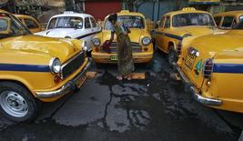 Sumitra Sarkar, 35, cleans a yellow ambassador taxi at a parking area along a roadside in Kolkata March 8, 2014. REUTERS/Rupak De Chowdhuri/Files
