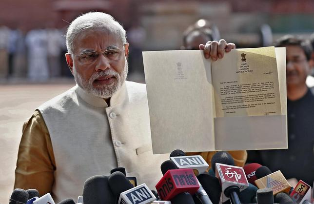 Hindu nationalist Narendra Modi, who will be the next prime minister of India, shows to the media a letter which he received from India's President Pranab Mukherjee after meeting him at the Presidential Palace in New Delhi May 20, 2014. REUTERS/Adnan Abidi