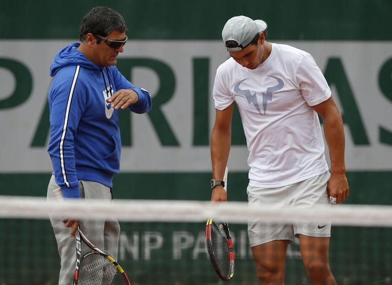 Rafael Nadal of Spain listens to his coach Toni Nadal during a training session for the French Open tennis tournament at the Roland Garros stadium in Paris May 24, 2014. REUTERS/Gonzalo Fuentes