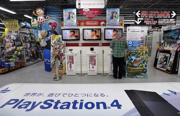 A man tries out Nintendo Co Ltd's 3DS portable game console near an advertisement for Sony's PlayStation 4 game console at an electronics retail store in Tokyo May 7, 2014.  REUTERS/Toru Hanai