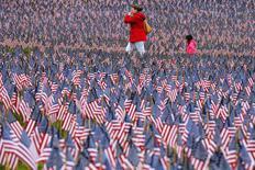 Unas personas avanzan en un campo tapizado por la ONG Military Heroes de Massachusetts  con banderas estadounidenses en Boston, mayo 24 2014. Don Skinner, un veterano de guerra de la Fuerza Aérea estadounidense, se levanta con la primera luz del amanecer, se toma su pastilla para el colesterol y un café instantáneo y enciende su computadora para pasar ocho horas al día contando historias de guerra sobre caídos que ya no pueden narrarlas. REUTERS/Brian Snyder