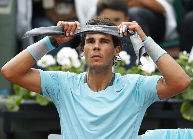 Rafael Nadal of Spain puts on a headband during his men's singles match against Robby Ginepri of the U.S. at the French Open tennis tournament at the Roland Garros stadium in Paris May 26, 2014. REUTERS/Vincent Kessler