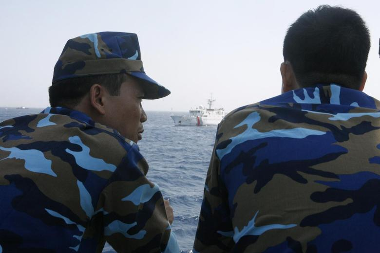 Officers of the Vietnamese Marine Guard talk as they monitor a Chinese coast guard vessel (top) on the South China Sea, about 210 km (130 miles) offshore of Vietnam May 15, 2014. REUTERS/Nguyen Minh