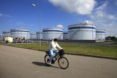 Женщина проезжает на велосипеде мимо нефтяного терминала в порту Клайпеды 21 июня 2010 года. Литва близка к подписанию своего первого контракта на покупку сжиженного природного газа (СПГ) у норвежской Statoil, что положит конец монополии Газпрома на литовском газовом рынке. REUTERS/Ints Kalnins