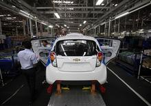 Employees work on a Chevrolet Beat car on an assembly line at the General Motors plant in Talegaon, about 118 km from Mumbai September 3, 2012. REUTERS/Danish Siddiqui/Files