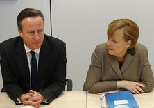 Britain's Prime Minister David Cameron (L) and Germany's Chancellor Angela Merkel meet at the start of the second day of a European leaders summit in Brussels March 21, 2104. REUTERS/Yves Herman