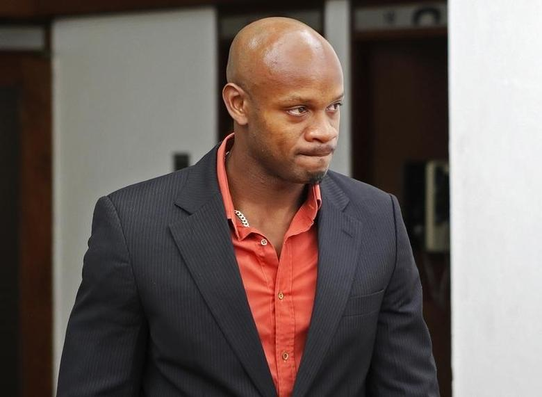 Jamaica's Olympic runner Asafa Powell, who tested positive for doping at the Jamaican Championships in 2013, takes a lunch break on the first day of his hearing before the country's anti-doping commission in Kingston January 14, 2014. REUTERS/Gilbert Bellamy
