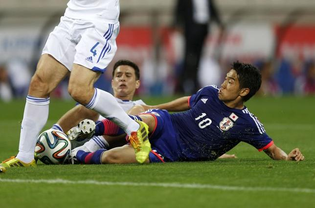 Japan's Shinji Kagawa (R) fights for the ball against Cyprus's Angelis Charalambous (C) during their international friendly soccer match in Saitama, north of Tokyo May 27, 2014. REUTERS/Issei Kato