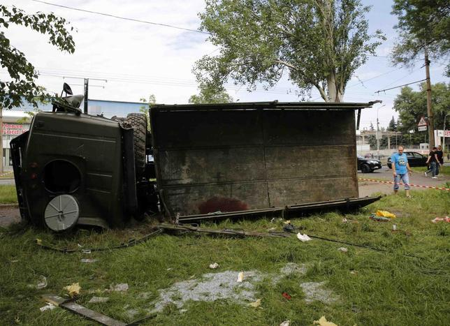 Locals walk by a wrecked rebel truck in a Donetsk neighborhood May 27, 2014. REUTERS/Yannis Behrakis