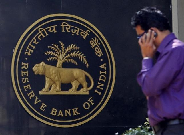 A man makes a phone call while standing near a Reserve Bank of India (RBI) crest at the RBI headquarters in Mumbai January 29, 2013.  REUTERS/Vivek Prakash/Files