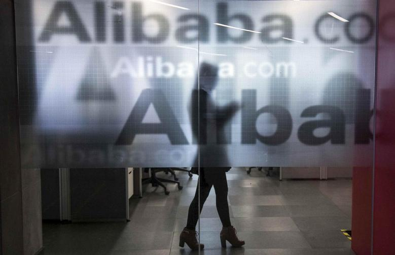 An employee is seen behind a glass wall with the logo of Alibaba at the company's headquarters on the outskirts of Hangzhou, Zhejiang province, April 23, 2014. REUTERS/Chance Chan