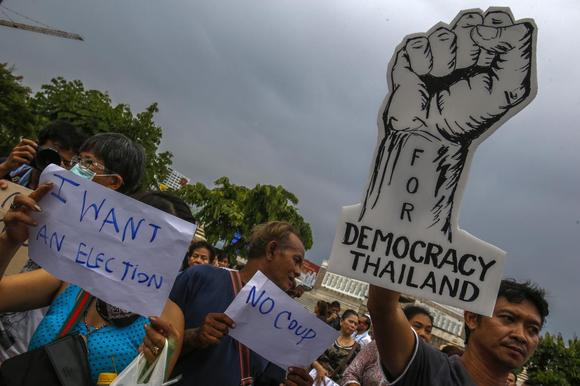 Demonstrators hold up signs during a protest against military rule at Victory Monument in Bangkok May 27, 2014.  REUTERS/Athit Perawongmetha