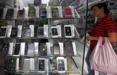 Imagen de archivo de una mujer junto a una tienda de teléfonos móviles en Sao Paulo, abr 23 2014. El índice de confianza de la industria brasileña retrocedió un 5,1 por ciento en mayo respecto a abril, mientras que el índice de confianza de los servicios bajó un 5,7 por ciento en el mismo período, en la mayor caída desde diciembre del 2008 para ambas lecturas, dijo el miércoles la privada Fundación Getúlio Vargas. REUTERS/Paulo Whitaker