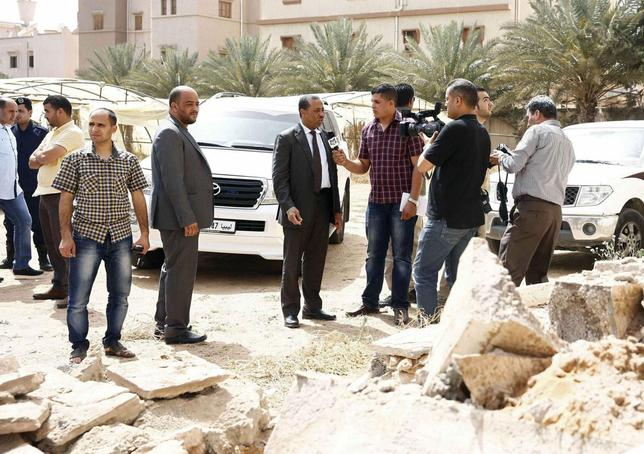 Libya's acting prime minister Abdullah al-Thinni (C) speaks to the media while visiting the Salah Eddin district after explosions took place at midnight, in Tripoli May 21, 2014. REUTERS/Stringer