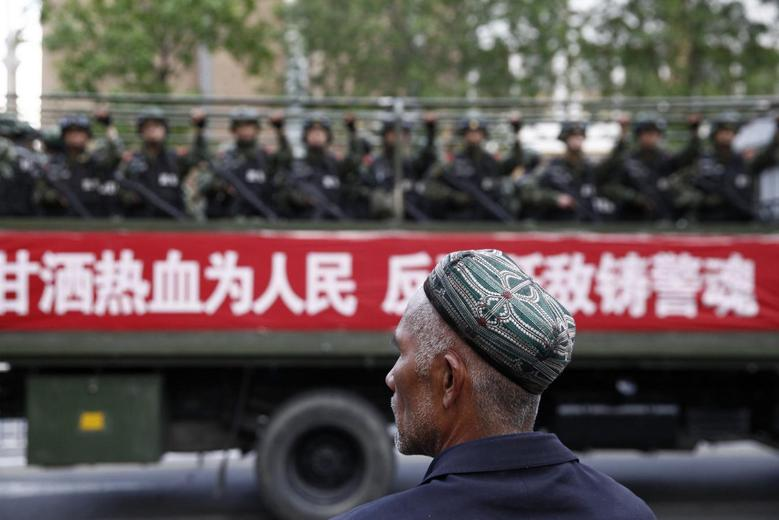 A Uighur man looks on as a truck carrying paramilitary policemen travel along a street during an anti-terrorism oath-taking rally in Urumqi, Xinjiang Uighur Autonomous Region May 23, 2014.  REUTERS/Stringer