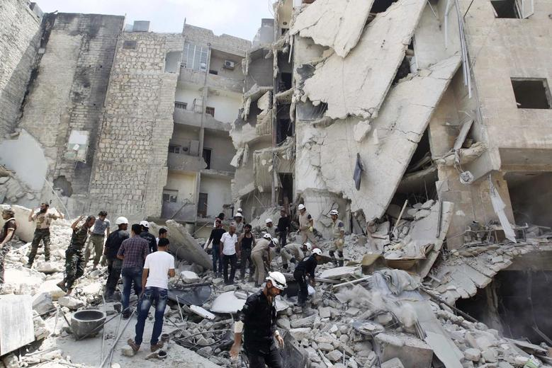 Civil Defence members, rebel fighters and civilians search for survivors at a site hit by what activists said was a barrel bomb dropped by forces loyal to Syria's President Bashar al-Assad in al-Qarlaq neighbourhood of Aleppo May 29, 2014. REUTERS/Jalal Al-Mamo