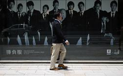 A man walks past a display window of a luxury brand at Tokyo's Ginza shopping district May 29, 2014. REUTERS/Yuya Shino
