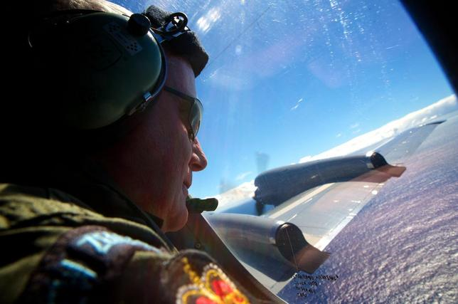 Seargent Trent Wyatt looks out an observation window aboard a Royal New Zealand Air Force (RNZAF) P3 Orion maritime search aircraft as it flies over the southern Indian Ocean looking for debris from missing Malaysian Airlines flight MH370 April 11, 2014.  REUTERS/Richard Wainwright/Pool