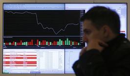 Мужчина на фоне информационного табло на Московской бирже 14 марта 2014 года. Российские фондовые индексы в течение последней сессии мая преимущественно снижались, а сделки с акциями Алросы и ФСК обусловлены вступлением в силу нового состава популярного индекса MSCI Russia после сегодняшнего закрытия торгов. REUTERS/Maxim Shemetov