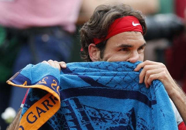 Roger Federer of Switzerland wipes his face with a towel during his men's singles match against Dmitry Tursunov of Russia at the French Open tennis tournament at the Roland Garros stadium in Paris May 30, 2014. REUTERS/Gonzalo Fuentes