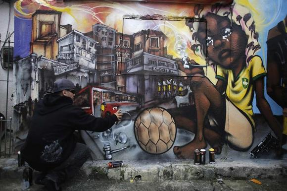 Brazilian artist Bone, a member of OPNI, puts the final touches to his graffiti on a wall, in reference to the 2014 World Cup, in the Vila Flavia slum of Sao Paulo May 28, 2014. REUTERS/Nacho Doce