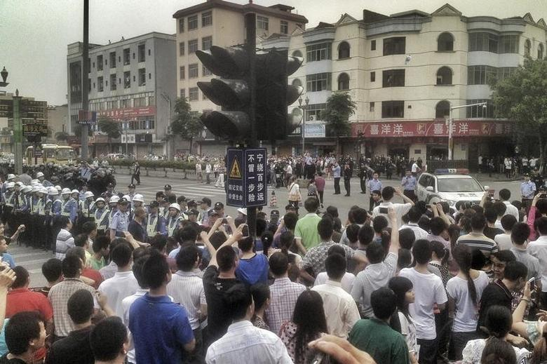 Workers protest during a strike as police stand guard at a crossroads near the factory area of Yue Yuen Industrial, in Dongguan, Guangdong province April 18, 2014. The strike at Yue Yuen - which says it is the world's largest branded footwear manufacturer, making over 300 million pairs of shoes last year - is not just one of China's biggest in recent years, it's also more clearly driven by workers' fears that they have been scammed by an opaque and convoluted welfare payment system. Picture taken April 18, 2014. REUTERS/Stringer (CHINA - Tags: CIVIL UNREST BUSINESS EMPLOYMENT) CHINA OUT. NO COMMERCIAL OR EDITORIAL SALES IN CHINA - RTR3LUBO