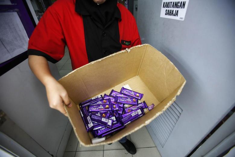 An employee shows a box containing Cadbury Dairy Milk Hazelnut and Cadbury Dairy Milk Roast Almond, to be return tomorrow in a shop in Shah Alam, outside Kuala Lumpur May 27, 2014.  REUTERS/Samsul Said