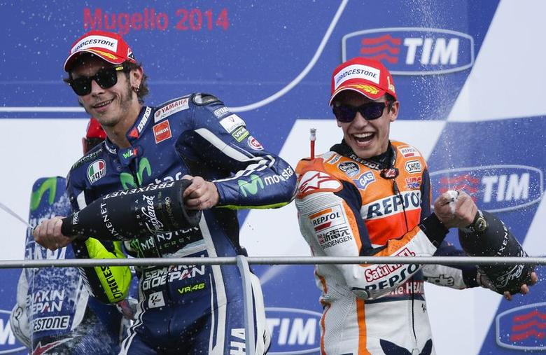 Honda MotoGP rider Marc Marquez of Spain (R) celebrates on the podium next third classified Yamaha Valentino Rossi of Italy after winning the Italian Grand Prix in Mugello circuit in central Italy June 1, 2014. REUTERS/Max Rossi