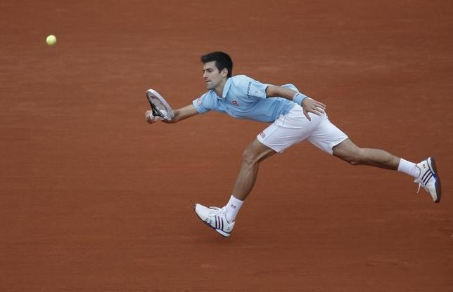 Novak Djokovic of Serbia stretches out to return a shot to Jo-Wilfried Tsonga of France during their men's singles match at the French Open tennis tournament at the Roland Garros stadium in Paris June 1, 2014.   REUTERS/Stephane Mahe