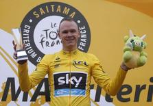 Team Sky rider and Tour de France winner Christopher Froome of Britain holds a trophy and a stuffed toy on a podium during a victory ceremony as he celebrates winning a criterium race in Saitma, north of Tokyo October 26, 2013. REUTERS/Yuya Shino