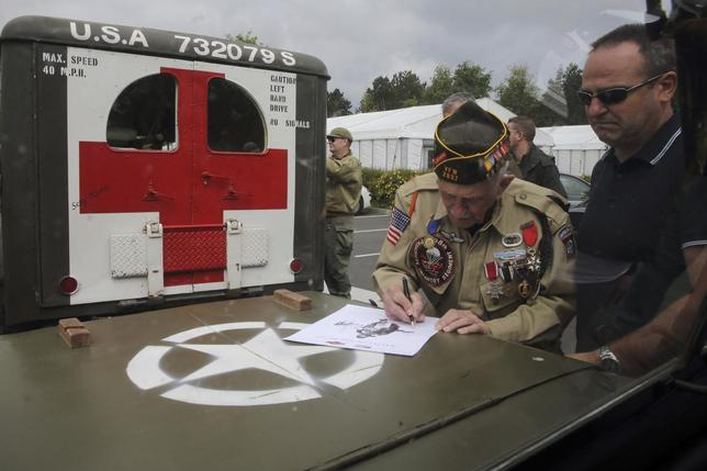 U.S. World War II veteran Jack W. Schlegel (L), 91 years-old, from Mount Tremper, New York, of the 508th Parachute Infantry Division of the 82nd Airborne who parachuted near Sainte-Mere-Eglise on June 6,1944, autographs a souvenir as he visits the American War cemetery in Colleville-sur-Mer, on the Normandy coast June 2, 2014. REUTERS/Pascal Rossignol