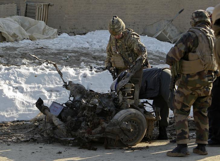 NATO troops investigate the the wreckage of a suicide bomber's car at the site of an attack in Kabul, February 10, 2014.  REUTERS/Omar Sobhani