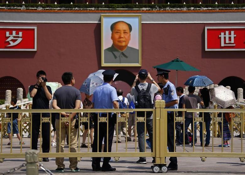 Policemen watch as tourists take pictures in front of the Tiananmen Gate, in Beijing, June 3, 2014. REUTERS/Petar Kujundzic