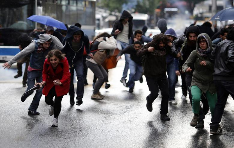 People run away from teargas fired during clashes between riot police and demonstrators during a protest in central Ankara June 1, 2014.  REUTERS/Umit Bektas