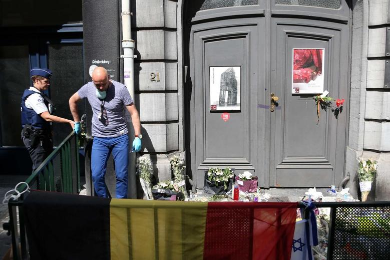 A federal crime scene investigator is seen next to a police officer at the entrance the Jewish Museum in Brussels June 2, 2014. REUTERS/Francois Lenoir