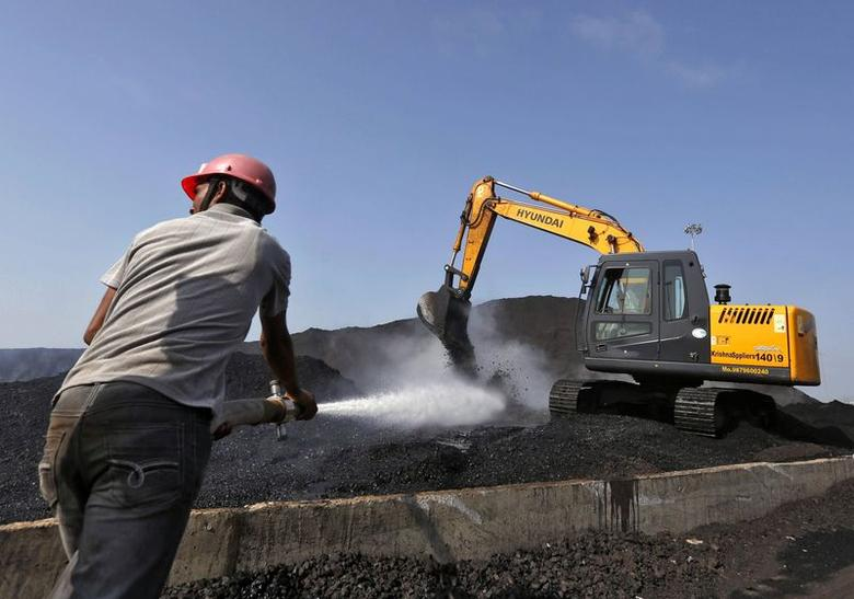 A worker sprays water over piles of coal as a bulldozer shifts coal at Mundra Port Coal Terminal in Gujarat April 2, 2014. REUTERS/Amit Dave/Files